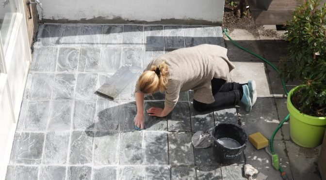 Klusvrouw Nicole Prins legt flagstones in cement