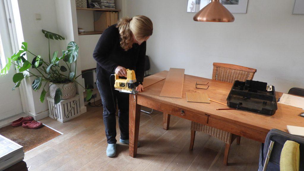Nicole saws a plank with a jigsaw.